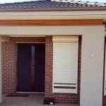 brick wall hours with cream white roller shutters brown stripes