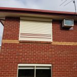 cream white roller shutter with red stripes on brick house