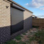 plain black roller shutter on brick wall
