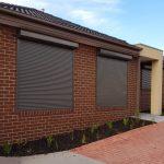 plain dark grey roller shutter on brick wall