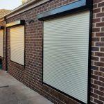 plain white roller shutter black railings on brick wall