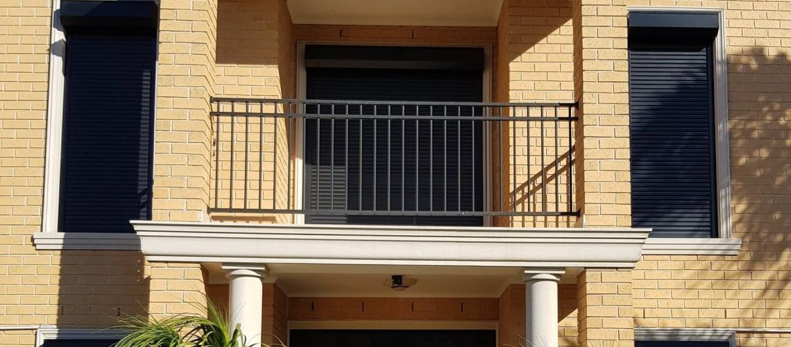 house entrance with black roller shutters on yellow bricks